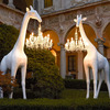 Life-Size Giraffe Statue Holding a Chandelier In Its Mouth